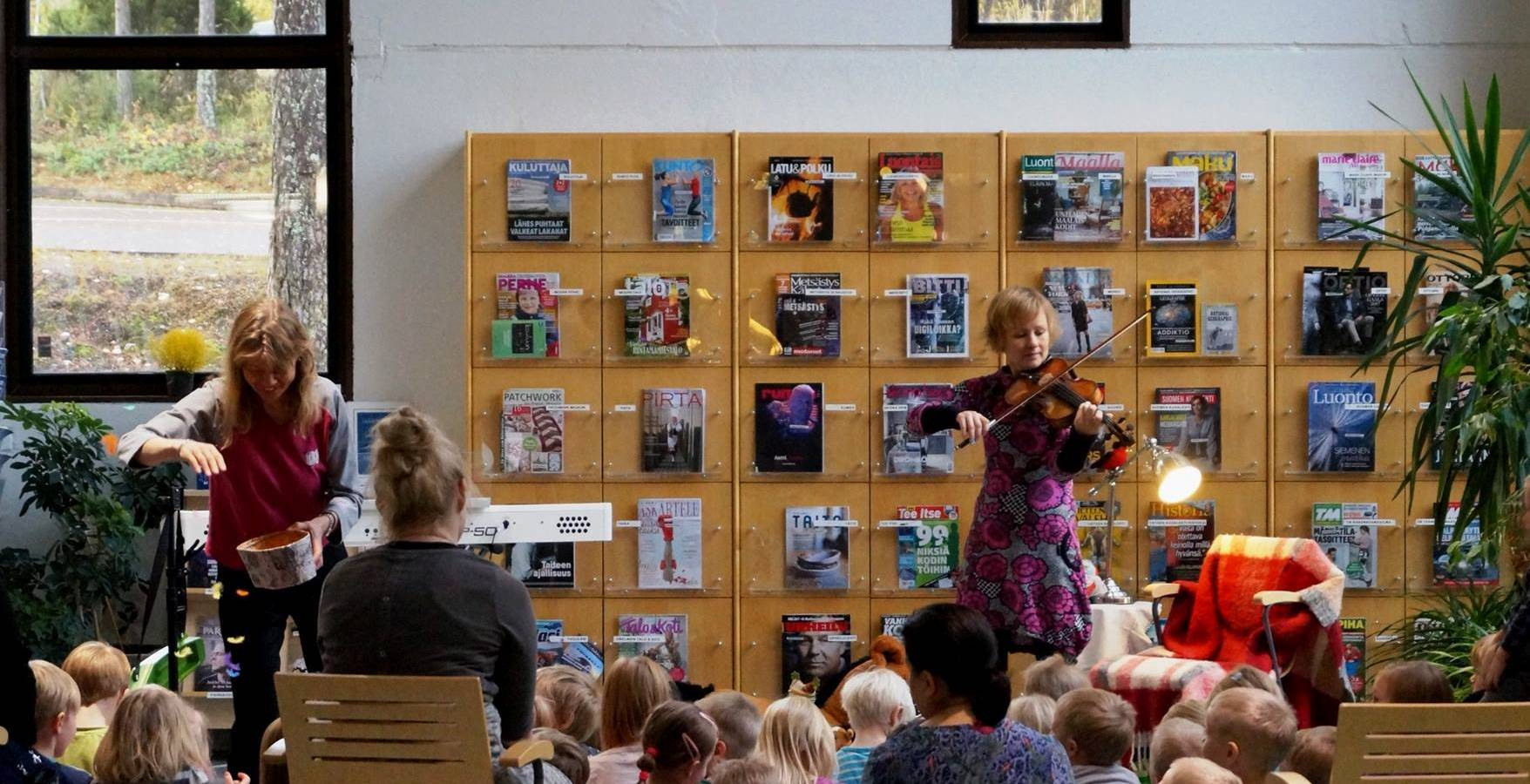 Musiikillinen satutunti lapsille: viulunsoittaja ja satutäti esiintyvät lapsiyleisölle.
