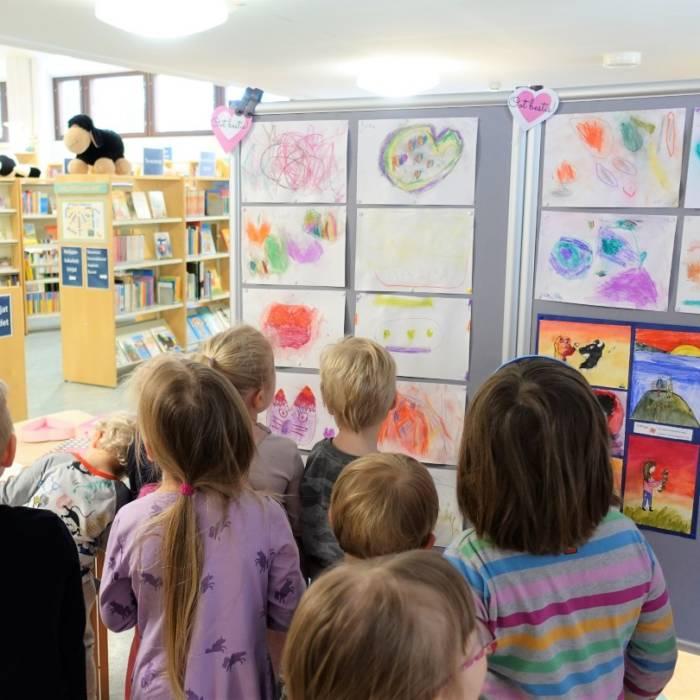 Lapset katsovat piirustusnäyttelyä